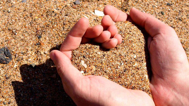 Händer bildar hjärta i sanden Foto: Nuwandalice by flickr.com