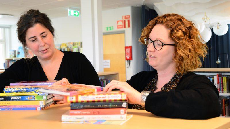 Bibliotekarierna Evelina Breslin och Jessica Åkerberg bläddrar i några av bibliotekets många böcker.