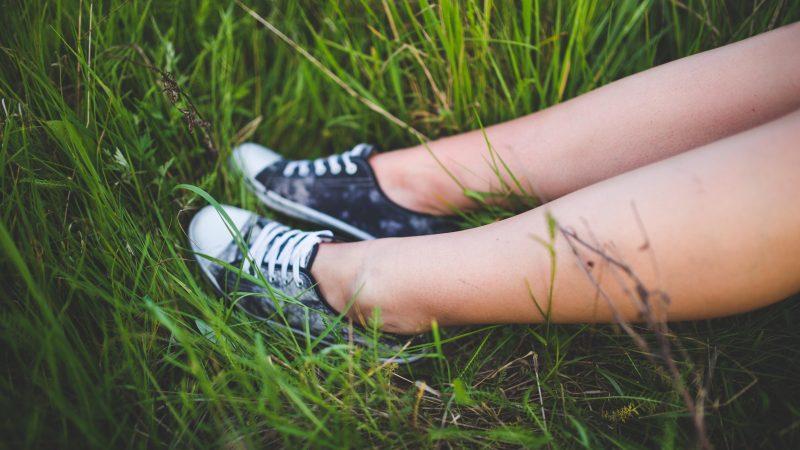 Tonåring sitter i gräset. Foto: Pixabay