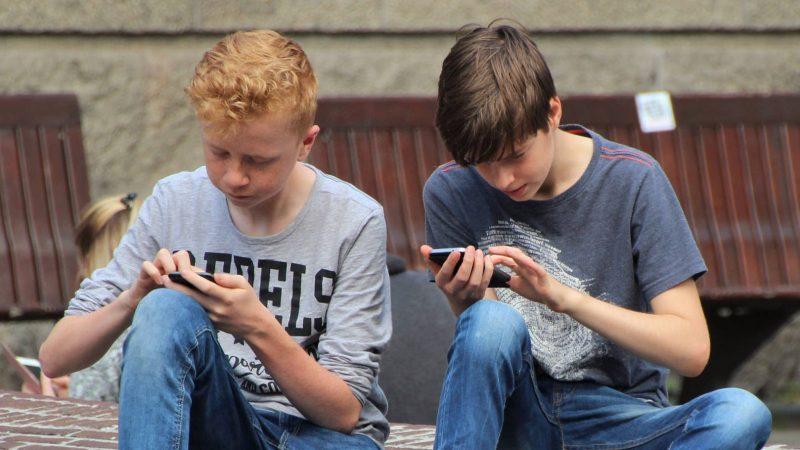 Två pojkar använder sina mobiltelefoner. Foto: Pixabay