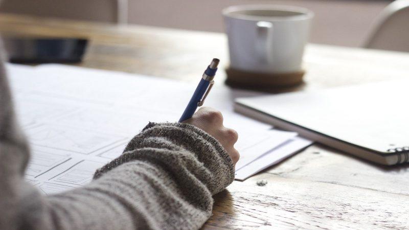 Foto av en hand som håller i en penna och skriver något på papper. Foto: Free-Photos från Pixabay