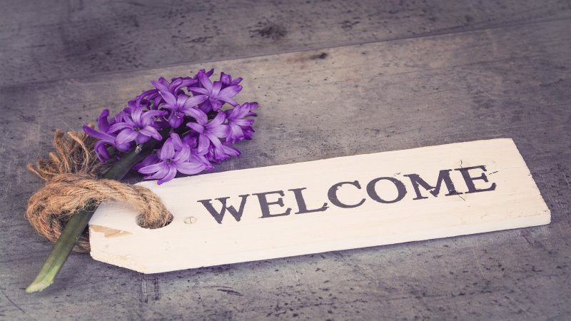Välkomstskylt med en blomma. Foto: Pezibear från Pixabay