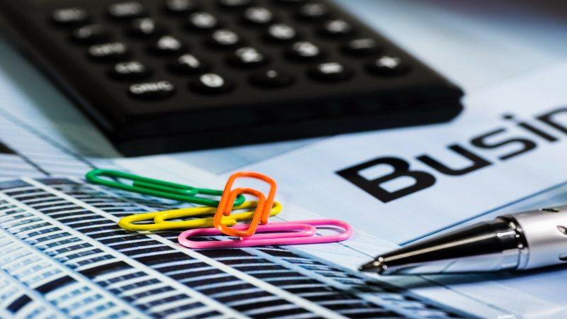 Foto av kontorsmaterial som miniräknare, papper, penna och gem. Foto: AlexanderStein från Pixabay
