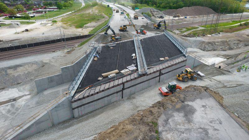 En ny motorvägsbro sätts på plats. Flera arbetsfordon med grävskopor häller ut stenar och makadam runt om den nya motorvägsbron.