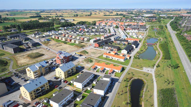 Flygbild över bostadsområdet Vikhem. På bild syns vita villor, röda tegelradhus och grönområden.