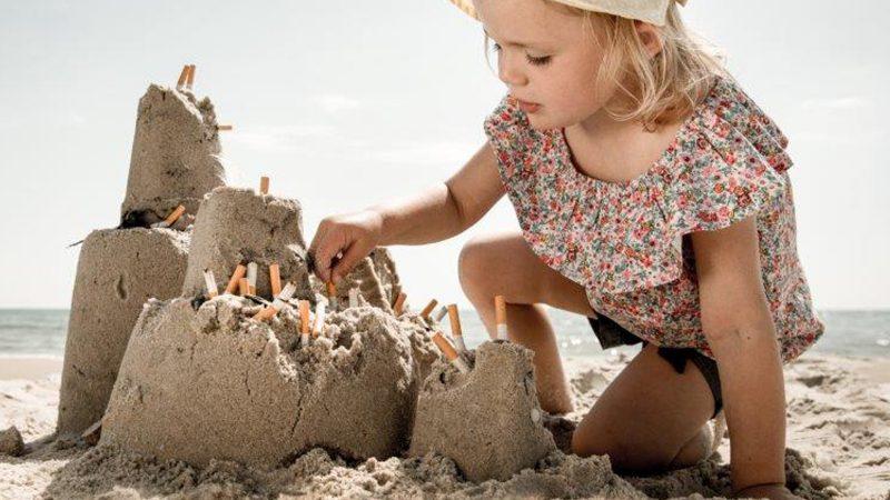 Flicka på en strand sätter cigarettfimpar i ett sandslott.