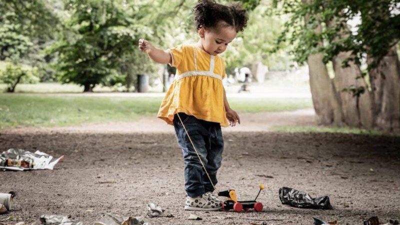 Flicka leker i en park full av skräp på marken.