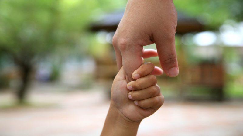 Hand i hand; barn och vuxen.