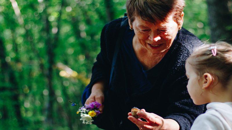 Kvinna visar ett snäckskal för ett barn.