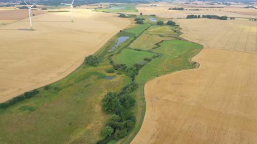 Höje å som rinner genom ett jordbrukslandskap.
